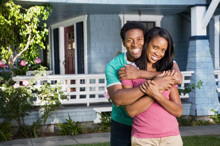 A sweet couple in front of their house.