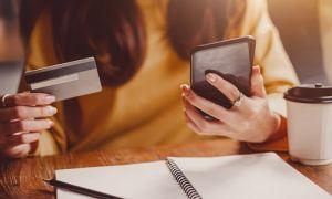 Woman holding debit card on phone