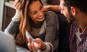 Woman smiling holding debit card
