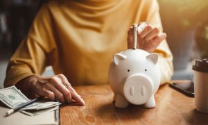 Woman puting money in piggy bank